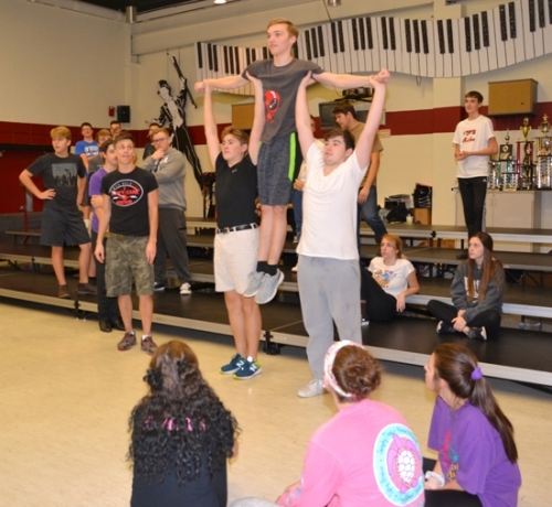 "Choreographer Jason Johnson (front, far left) watches as Varsity Singers members William Borland (left) and Hunter Lee (right) lift Anthony Bryant into the air during rehearsal on Thursday, Nov. 2, for the song ""Under the Sea,"" one of the numbers featured in the show choir's Disney-themed Pomp & Plenty performance on Nov. 18 and 19."