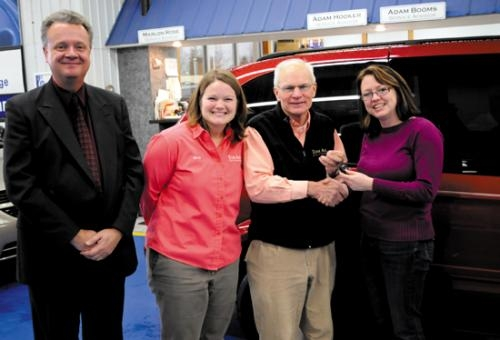 Mindi Ahl (second from left), 2007 Huntington University graduate and business manager at Tom Ahl Chrysler, Dodge, Jeep in Lima, OH, and Tom Ahl (third from left), owner of the dealership, present van keys to Grace McBrayer (right)