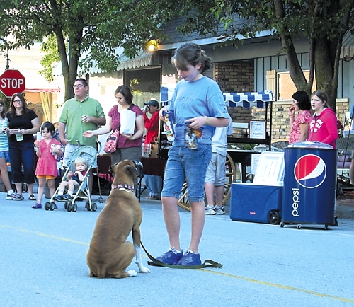 Taylor Scher, a member of the Waggin' Tails 4-H dog club, and her boxer Kallie demonstrate their skills during a program at the Farmers Market in Roanoke last summer. The club will hold an open house for prospective members on Feb. 27 at 6:30 p.m.