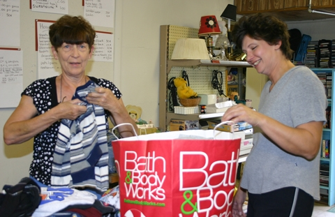 Nancy Surfus, left, helps bag up Christy McCarver's clothing during her visit to the Bargain Basement on Friday, August 28. The store is open on Fridays and Saturdays from 9 a.m. to 4 p.m. in the basement of the Knight-Bergman Civic Center in Warren.