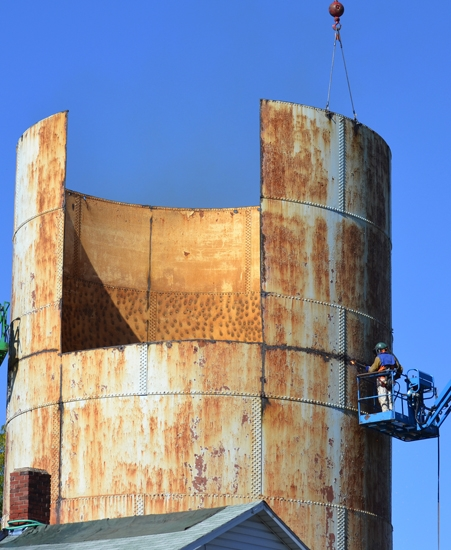 Crews from Iseler Demolition dismantle a century-old water storage tank on Oak Street, in Huntington, on Tuesday, Oct. 8.