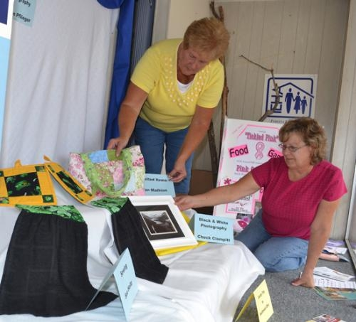 Huntington County Extension Homemakers Rita McCabe (left) and Valerie Birkhold set up a downtown window display showcasing the organization in observance of Extension Homemakers Week, which is being observed this week.