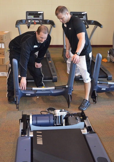 Parkview Huntington YMCA Fitness Director Todd Latta (left) and Scott Craft, personal trainer, check out a new treadmill slated to be installed at the facility on Thursday, April 4. The YMCA added and upgraded 22 new pieces of equipment.