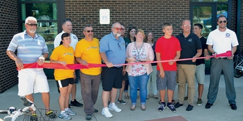 Representatives and sponsors of the Zagster bike share program get ready to cut the ribbon at the Huntington Branch of the Huntington City-Township Public Library on Saturday, June 25. Pictured (from left) are Ron Kline, partner with Spokesman Cycling;  Kelly Frank, event coordinator for HARTA; Bob Caley, City Services superintendent; Jim Lewis, vice president of HARTA; Mayor Brooks Fetters; Greg Smitley, Huntington University vice president for business and finance/treasurer; Amber Hudson, library employee; Beka Lemons, library director; Devon Henderson, library employee; Aiden Klausing, mayor for the morning; Vince Haupert, Huntington University vice president of advancement; Kole Hale, Zagster employee; and Andrew Rensberger, Parks Department community engagement volunteer/coordinator.