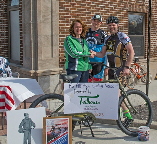 Rachel Zahm (left), coordinator of the Vietnam Veterans Memorial Bicycle Ride, and Barry McManus (center), of Trailhouse Village Bicycles in Winona Lake, present a bicycle to raffle winner CJ Stoltie (right), of Fort Wayne. McManuss donated the bicycle for the raffle.