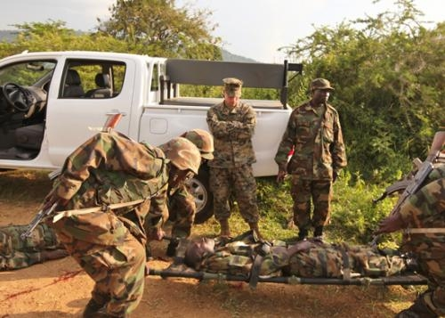 Sgt. Timothy McCoy (left), of Roanoke, a member of the United States Marine Corps, evaluates soldiers with Uganda People's Defense Force on their tactical combat casualty care during a training exercise held June 25 in Kakola, Uganda.