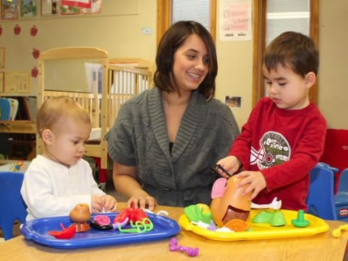 Katie Schwab (center) plays with her sons Elijah (left) and Bradley at Pathfinder Kids Kampus, in Huntington. Schwab's children are enrolled in the child care center's Early Head Start program.