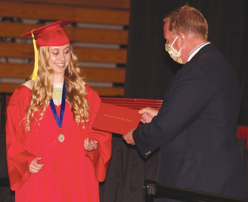 Grace Dimond, a 2020 Huntington North High School graduate, receives her diploma at North Arena on May 29, 2020. HNHS took extra precautions to ensure that graduates could safely receive their diplomas during the COVID-19 pandemic, such as spreading out the graduation into timed shifts and cleaning hand rails between graduates.