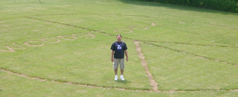 "Richard Williams stands in front of the peace sign etched in his back yard to the 1969 music festival Woodstock. Williams guesses the sign reaches between 60 and 70 feet across. His original peace sign was created in 2007 for the ""Summer of Love."""