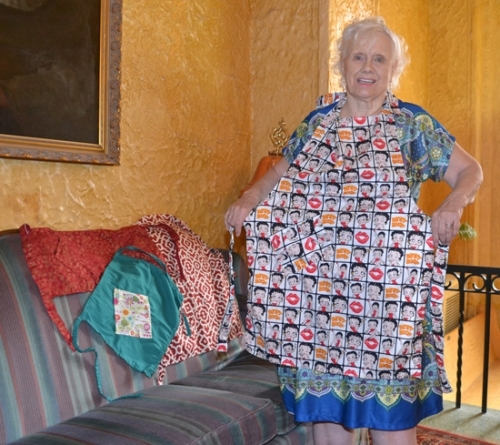 Roberta Rector models one of her cancer-fighting aprons, with more aprons laid out on a sofa in the lobby of the LaFontaine Center.