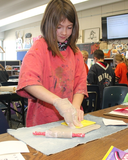 Karissa Kaiser, 9, a third grade student at Northwest Elementary School, presses a leaf-shaped stamp into a fresh clay tile on Wednesday, April 13, as she prepares her portion of the clay tile mural that will celebrate Indiana's 200th birthday. About 450 HCCSC elementary school students will contribute to the project, which has been endorsed by the State Bicentennial Commission.