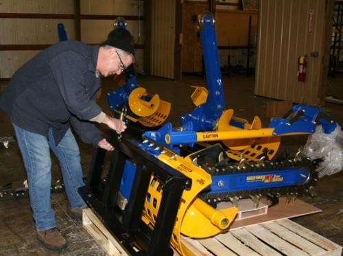 Todd Miller, president of Auger Torque USA, LLC, attaches a hose guide to a trencher machine Thursday, Jan. 9. The UK-based company planted a location in Huntington in 2013 and expects to employ as many as 35 workers in the next five years.