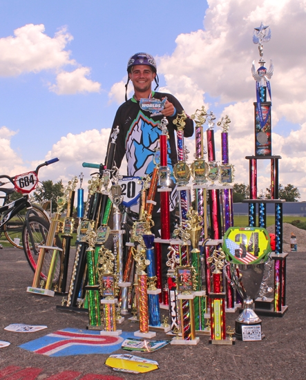 Paul Bickel, of Huntington, stands surrounded by trophies he's won since becoming a BMX racer a year ago. While the 22-year-old travels around the country to races, he also works to raise the sport's profile in Huntington, having helped build the new BMX track in Yeoman Park.