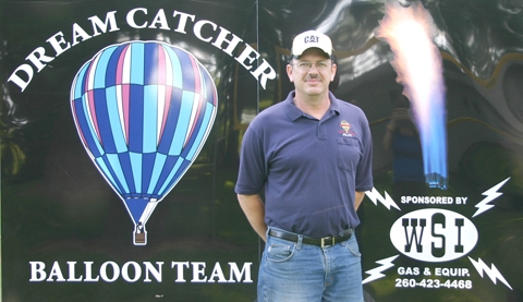 "Chris Smart, of Huntington, stands in front of the trailer for ""The Dreamcatcher,"" the host air balloon he pilots in competitions in the area and locally durng passenger rides."