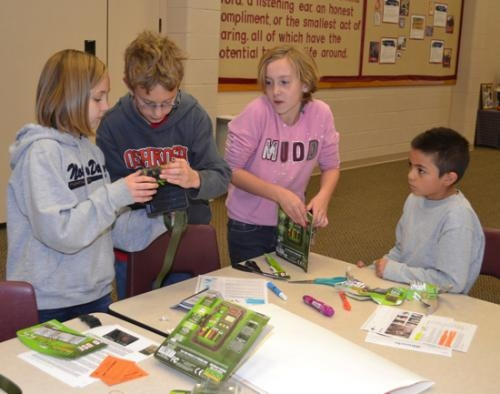 Lincoln Elementary School students (from left) Courtney Hale, Matthew Kline, Megan Landon and Antonio Villa Lopez unwrap and assemble cameras they plan to use to watch for activity in the barn owl nests the class is placing around the county.