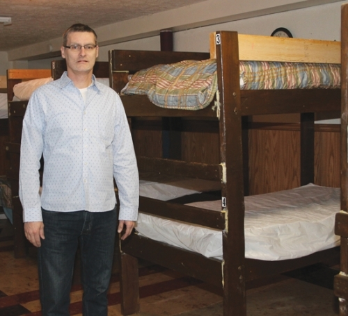 Rev. Jimi Staton stands in one of two sleeping rooms containing bunk beds in the basement of New Life Fellowship Church, in Huntington, which are open to anyone needing a warm place to sleep through February. The overnight shelter has seen a steady increase in people since it opened the first week of the new year.