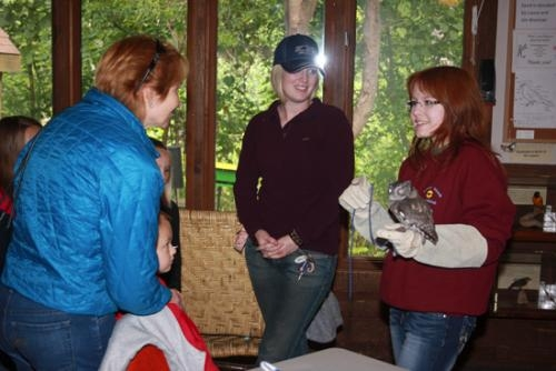 Alexandra Forsythe (right) shows off Hoodini, an eastern screech owl and permanent resident of Soarin' Hawk Raptor Rehab, to a group of adults and children after the facility's Race 4 Birds fund-raiser Sept. 13.