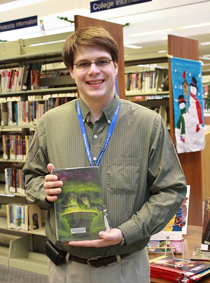 "Circulation Clerk Matt Etzel holds J.K. Rowling's ""Harry Potter and the Half-Blood Prince,"" the most checked-out adult and young adult fiction book of 2011 at the main branch of the Huntington City-Township Public Library."