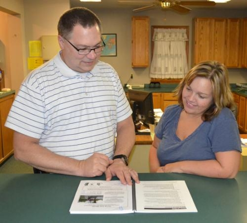Huntington City Services Superintendent Bob Caley peruses a booklet on how to hire an arborist with Kristi Bowman, City Services clerk. The City of Huntington has held Tree City USA status for 18 years.