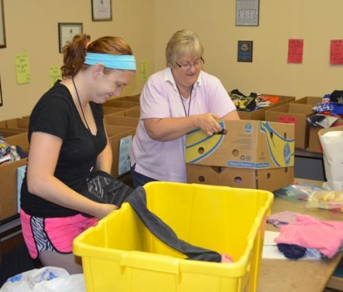 Taylor Hippensteel (left) and her mother Kelly, both volunteers at Love INC, work to get supplies ready for the Back to School Shopping event. The program provides school clothing and a backpack for area youth and will be held Aug. 1-3.