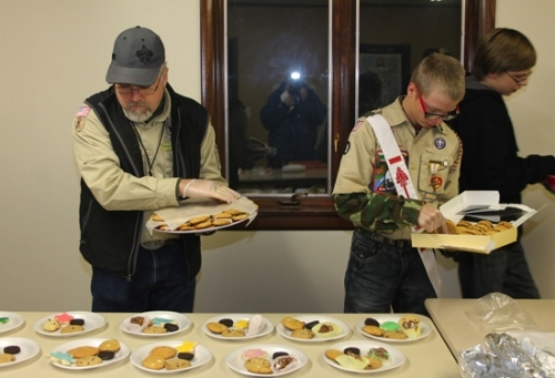 Boy Scout Troop 637 Scoutmaster Perry Harris (left) and Boy Scout Luke Christman fill plates with cookies baked by the troop. The plates of cookies were delivered to residents of the Huntington Retirement Community on Tuesday, Dec. 13. The Boy Scout troop has held the cookie giveaway for around eight years as a way of saying thank you and bringing cheer to the Seniors living in the apartment complex.