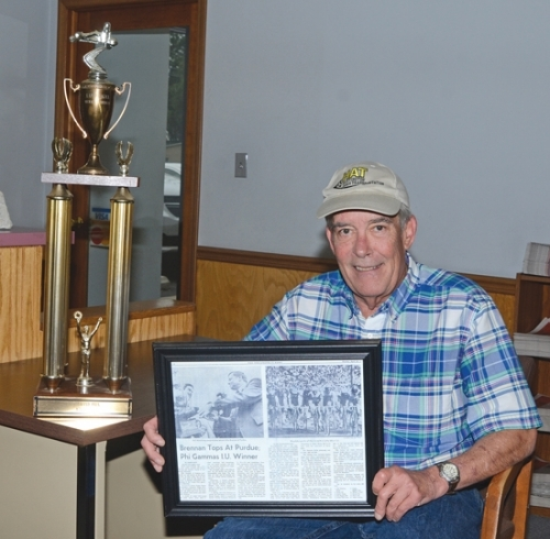 Mike Brennan, of Huntington County, sits next to the trophy he received for winning the Purdue Grand Prix in 1975. He is holding a copy of a newspaper article that was written about his victory. After the race, Brennan got to meet Neil Armstrong, who served as the event's grand marshal.