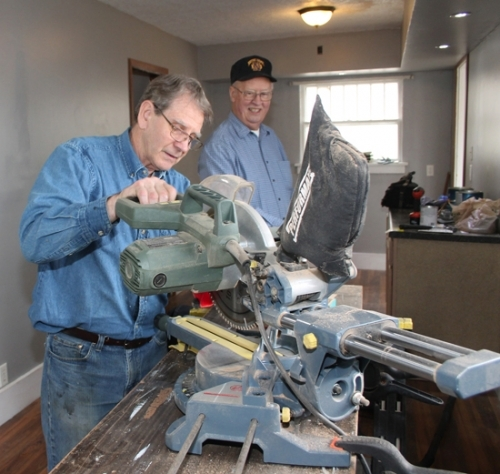 Love in the Name of Christ volunteer Dave Walker (left) mans the saw as Dick Widelski looks on. The two-man crew is renovating a house adjacent to the Love INC facility on Washington Street, which will become the new offices for the organization.