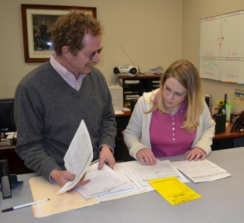 Mark Mussman (left), executive director of Huntington Countywide Department of Community Development, looks through some recent permit applications with Miranda Snelling, office coordinator.