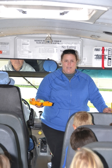 Bus driver Mandy Beaty, with fellow bus driver Bill Oswalt peering in the rearview mirror, uses a carton of eggs to show Northwest Elementary School students how they'll be jostled around if they don't stay in their seats on the bus.