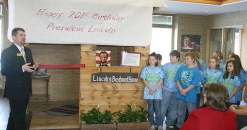 Lincoln Elementary School Principal Adam Drummond (left)  speaks to students, teachers and community members at the ribbon-cutting ceremony for a log cabin replica of Abrahm Lincoln's boyhood home.