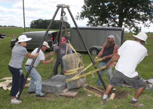 "Sheila Hines (far left) and (from left) Dennis Brewer, Bob Rose, John ""Walt"" Walters and Randy Jones work together to raise a tombstone that has been face down in the dirt for more than 50 years on Wednesday, Aug. 14, at Wesley Chapel Cemetery."