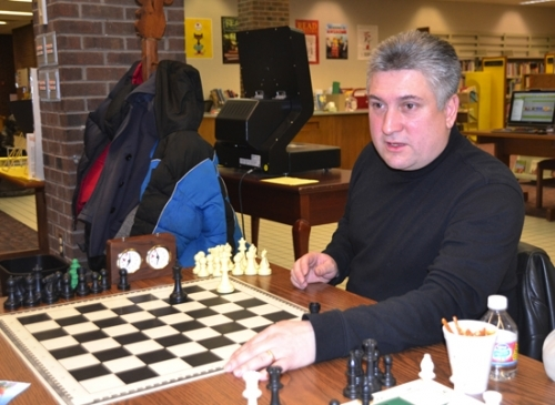 John Martinez explains a chess move to one of the members of the chess club he coaches. The club, an extension of Martinez's love of the game, meets monthly at the Huntington Branch of the Huntington City-Township Public Library.
