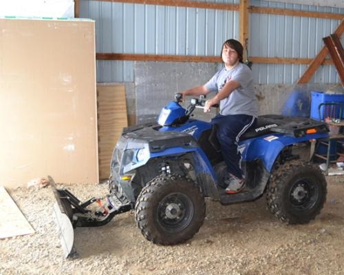 Cody Chesterman climbs on his four-wheeler, equipped with a blade so he can plow snow for hire this winter.