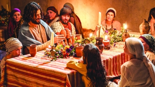 "Jonathan Roumie (third from left), who plays Jesus in ""The Chosen,"" entertains the children seated around at his table in a scene from the wedding at Cana. The crowd-funded series is available to view free of charge by downloading The Chosen app from the Apple App Store or Google Play."