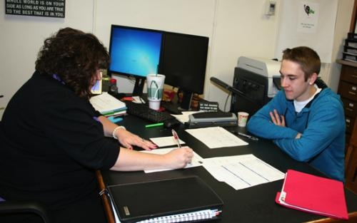 Huntington County Community Corrections Executive Director Leslie Rentschler (left) signs off on paperwork submitted by program participant Talon Lynch on Thursday, Feb. 20. Lynch is one of 11 active participants in the program.