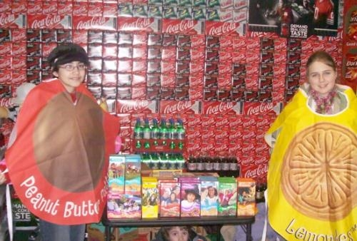 Girl Scouts Andrew Broxon (left) and Cheyanne Geiderman don cookie costumes to work at a cookie sales booth.