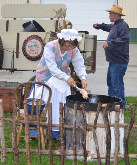 Po Brooks drops apple fritter batter into hot grease during a previous Forks of the Wabash Pioneer Festival as her husband, Jeff Brooks, works in the background. The Brooks family has been involved with the festival since its beginnings in 1975.