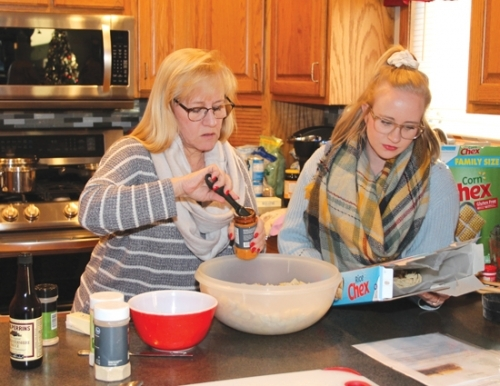 Ashley Burson (right) helps her mother, Susie Boyer, make one of the family's traditional Christmas treats Wednesday, Dec. 18, at Boyer's home in Roanoke. Burson, of Huntington, is on leave from her assignment as a missionary in Nigeria.