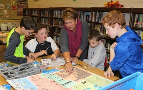 Lisa Merryman (middle), a coach for the Lancaster Elementary School robotics team, gives some of the team's members a helping hand as they try to construct a robot during a team meeting in the school's library on Tuesday, Nov. 22. Pictured are (from left) Joe Cobey, Kris Michaelson, Merryman, Alex Kelsey and Zach Bishop. The team, which is also coached by Vicky Platt, is in its first year at Lancaster.