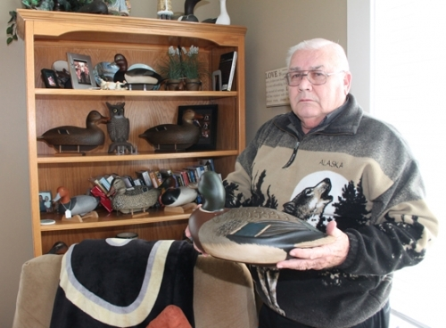 Burton Wygant, of Rural Roanoke, holds one of the prized decoys in his collection, a male mallard carved by Dark Feather Freeman. Wygant has reduced his collection down to about 250 decoys, all displayed throughout his home.