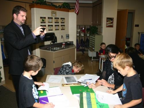 Lincoln Elementary School second grade teacher Jill Slagel (right) helps Noah Bruce (right, seated) with his writing workshop activity, as principal Adam Drummond (standing, left) takes a photo with his iPhone to share on the school's Twitter account.