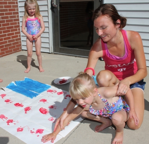 Kids Kampus Discoverers Class teacher Karissa Ditzler (right) helps Madison Yarger, 4, stamp her handprint on the flag mural during craft time Thursday, June 30.