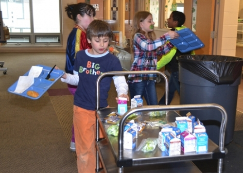 Lincoln Elementary School fourth-grader David Kendall places his unopened carton of milk on a tray of unwanted broccoli, cheese sticks and more milk before heading to the trash can in the school cafeteria. Lincoln is the first Huntington County school to join Food Rescue, which allows students to donate unwanted food to the food pantry at Love In the Name of Christ.