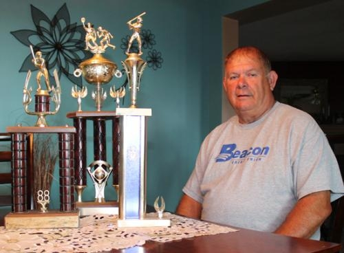 Kenny Foust, who has coached youth sports in Huntington for 35 years, sits with a few of the trophies his teams have earned during that time, each one from a different decade.