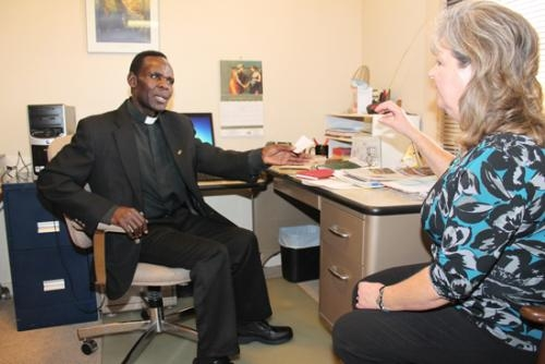 Rev. Sebastian Twinomugabi (left), associate pastor at SS. Peter and Paul Catholic Church, in Huntington, chats with church secretary Kelly Jennings at the church on Friday, Nov. 9.