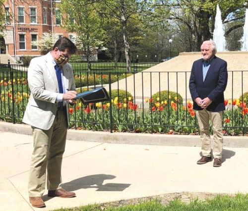 As Dr. Norris Friesen (right) stands by, Huntington Mayor Richard Strick signs the proclamation declaring May 8 as Norris Friesen Day. The ceremony honoring the retiring professor and administrator took place Friday, May 8, at Huntington University.