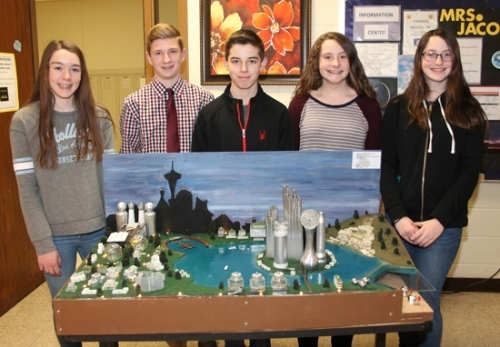 Team Acropolis, made up of (from left) Paige McCutcheon, Wyatt Couch, Tyson Thompson, Avery Drabenstot and Sophia Derico, proudly stand behind their model city, Acropolis, part of their award-winning Future City presentation that garnered them second place in the Indiana Regional preliminary competition on Jan. 20. The shadow in the background of the model is that of Seattle, WA, which provided the inspiration for their presentation.