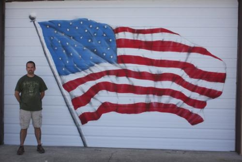 Josh Smith, chalk and airbrushing artist, stands next to an airbrushing of an American flag he created for Beth Hoffer for her birthday.