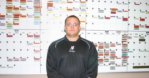 Huntington North High School Athletic Director Michael Gasaway stands in front of a large calendar of HNHS athletic events for the 2009-10 school year.