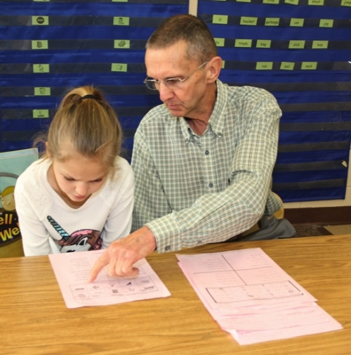 Volunteer George Richardson (right) helps Lancaster Elementary School first-grader Olivia Thomas, 7, with a difficult word as she reads aloud to him during class on Wednesday, March 29. Richardson volunteers the equivalent hours of a full-time employee, working year 'round at the school.